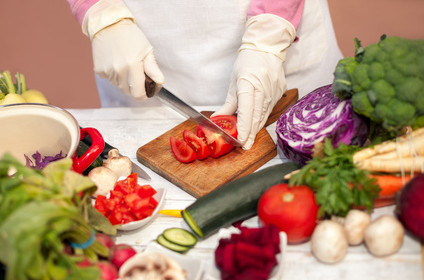 Woman with gloves slicing tomato on cutting board